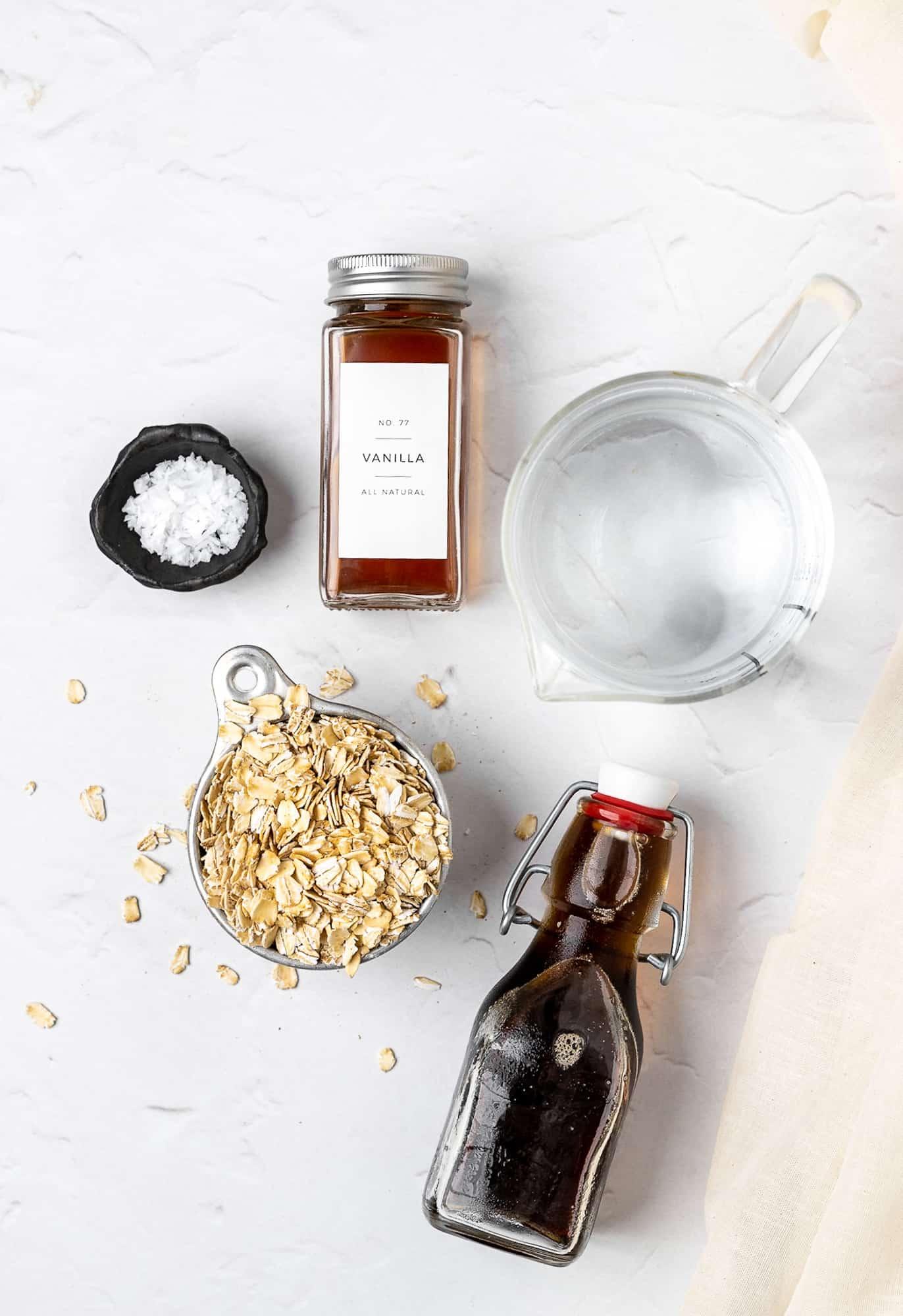 ingredients for homemade oat milk: oats. water, vanilla, maple syrup, sea salt