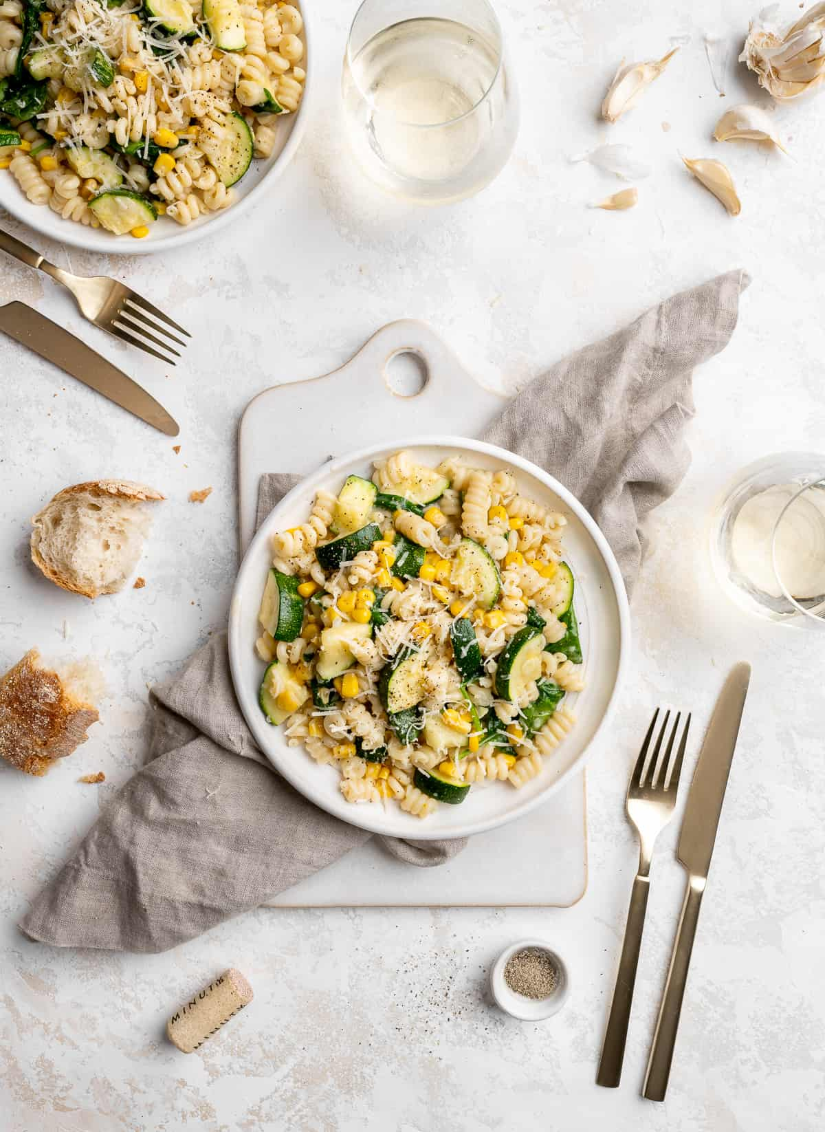 vegan creamy summer pasta with zucchini, corn and spinach on a white plate topped with parmesan cheese