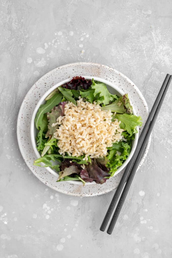 mixed lettuce and brown rice in a white bowl