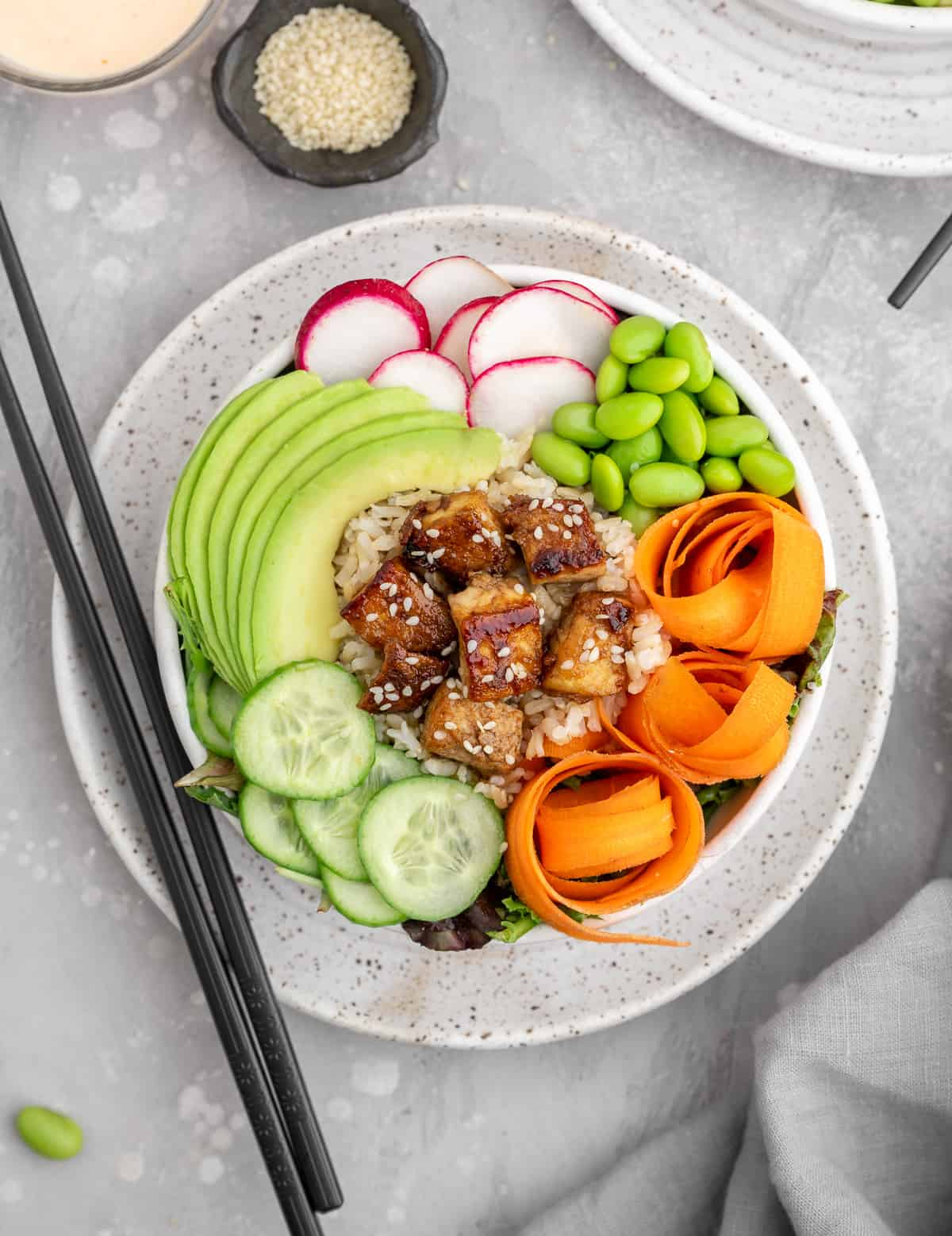 Sesame Ginger Tofu Poke Bowl in a white bowl with black chopstick next to it