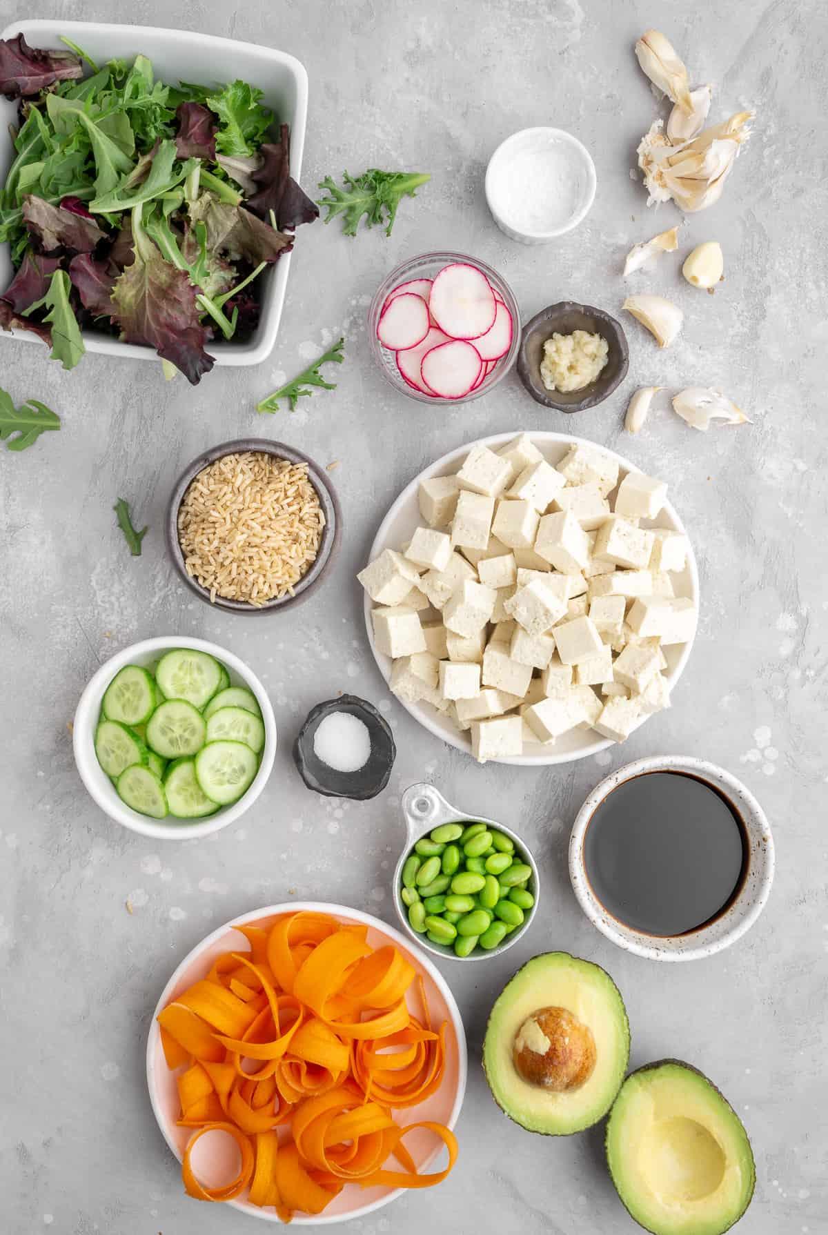 ingredients for vegan tofu poke bowl: avocado, carrots, edamame, cucumber, salt, sauce, tofu, lettuce, rice, ginger, garlic, radishes, corn starch