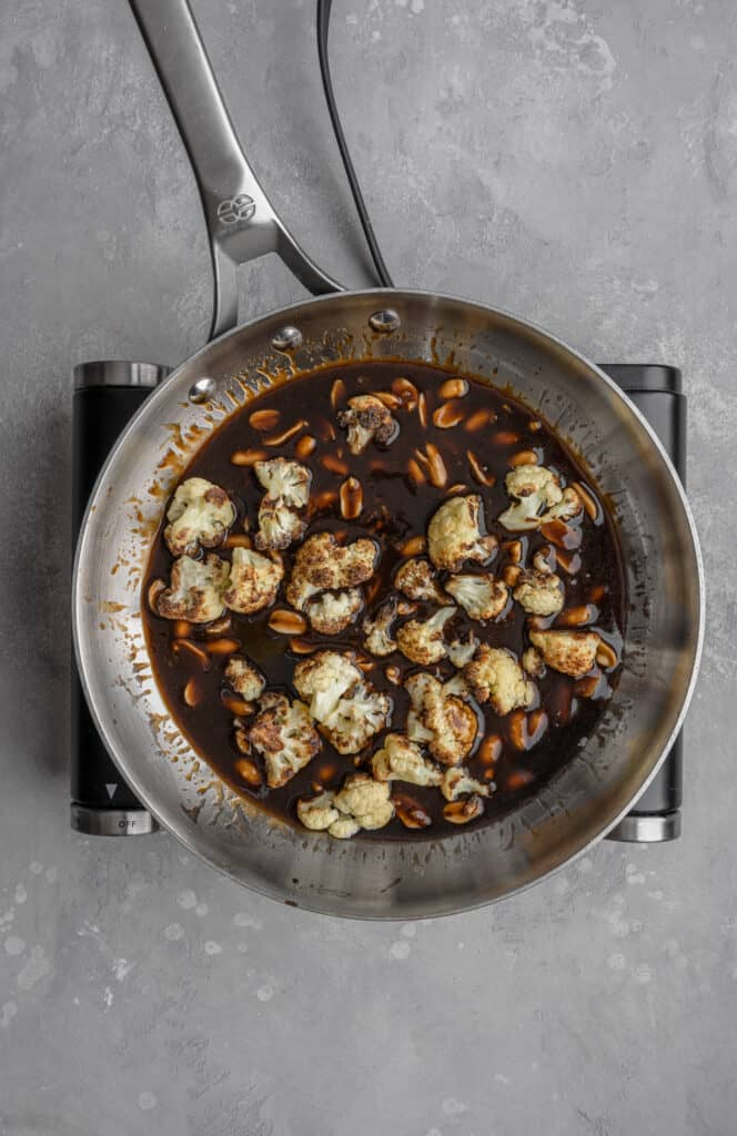 roasted cauliflower and peanuts in a vegan kung pao sauce in a stainless steel pan
