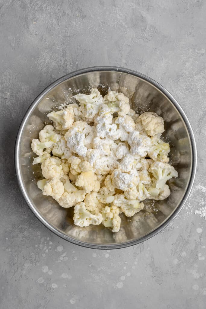 cauliflower in a bowl with oil and cornstarch