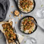 kung pao cauliflower on a black plate with a bed of basmati rice and topped with scallions
