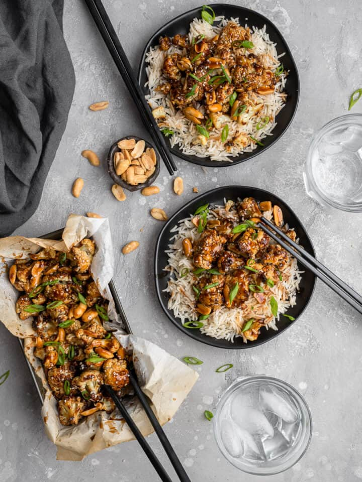 kung pao cauliflower on a bed of rice on a black plate with chop sticks