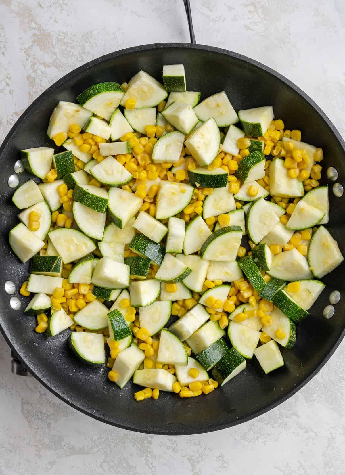 raw corn and raw zucchini in a pan