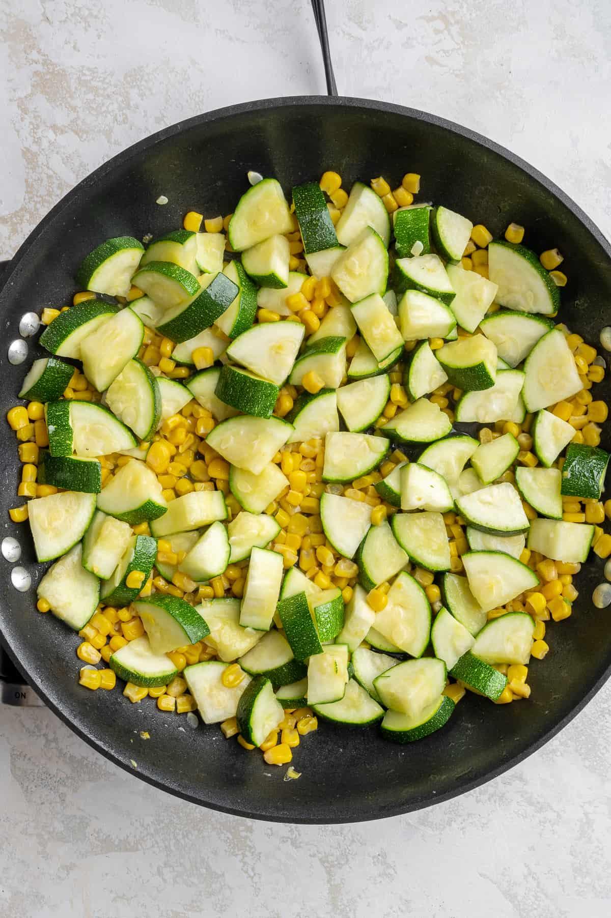 corn and zucchini sautéed in a pan