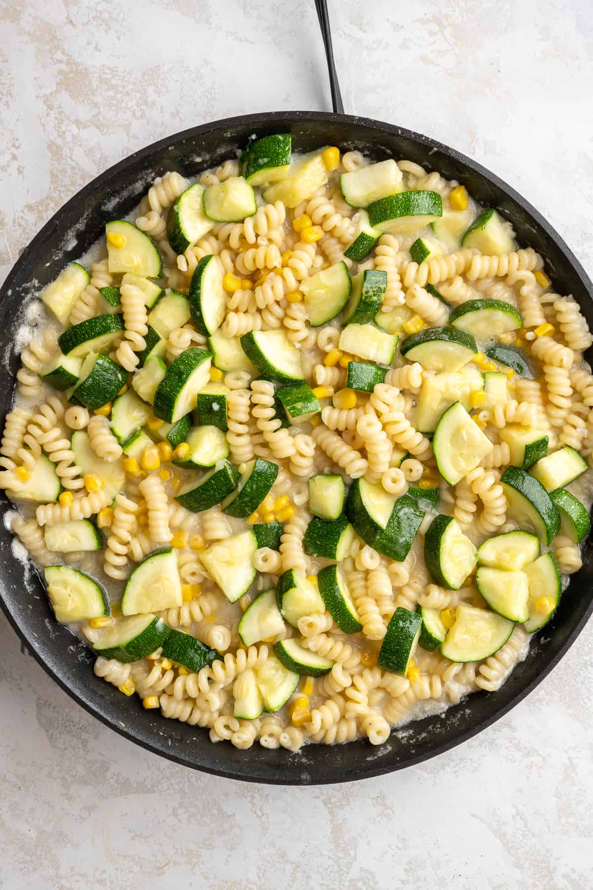 pasta with zucchini and corn being tossed in sauce in a pan