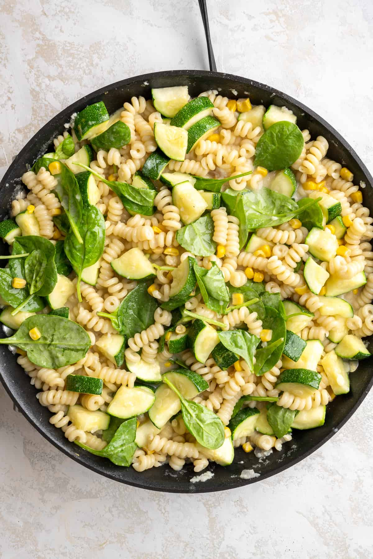 pasta with zucchini, spinach, and corn being tossed in a cream sauce in a pan