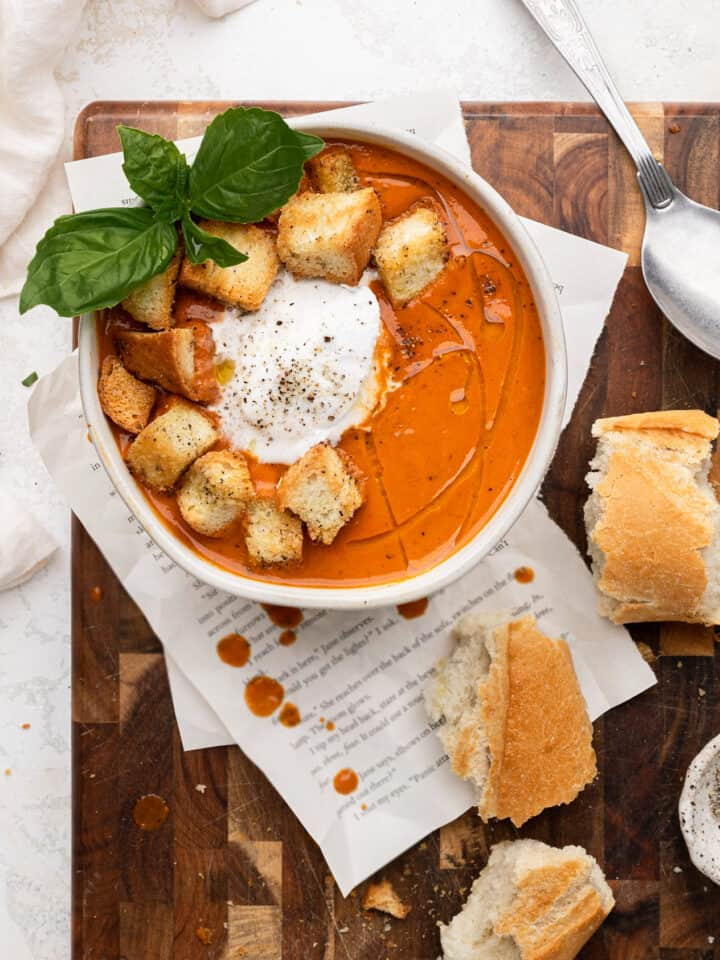 A bowl of creamy tomato soup topped with croutons, coconut cream, and basil
