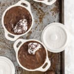 chocolate avocado mousse with a scoop of coconut cream on top divided into 3 white ramekins