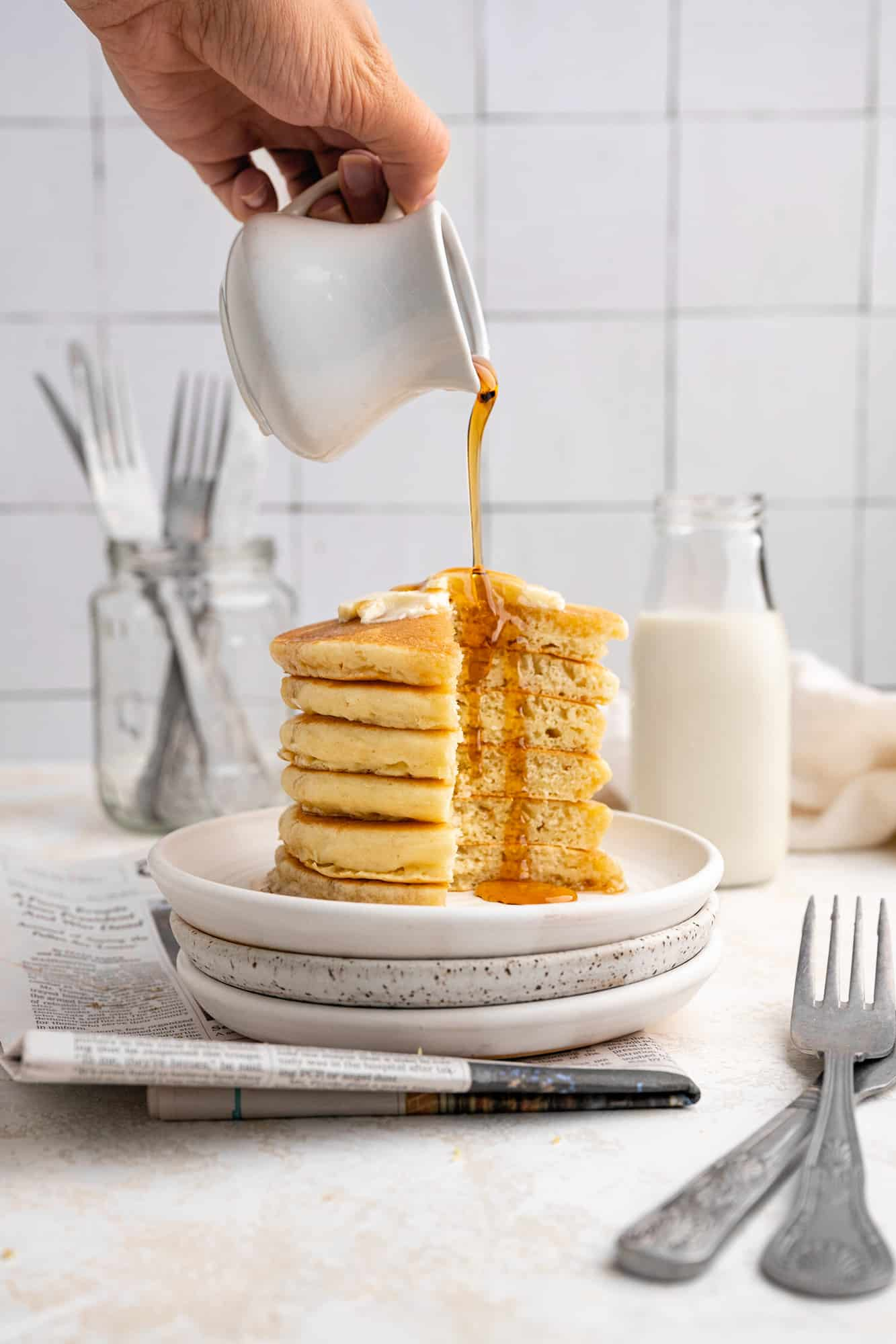 Stack of pancakes cut open with syrup being poured