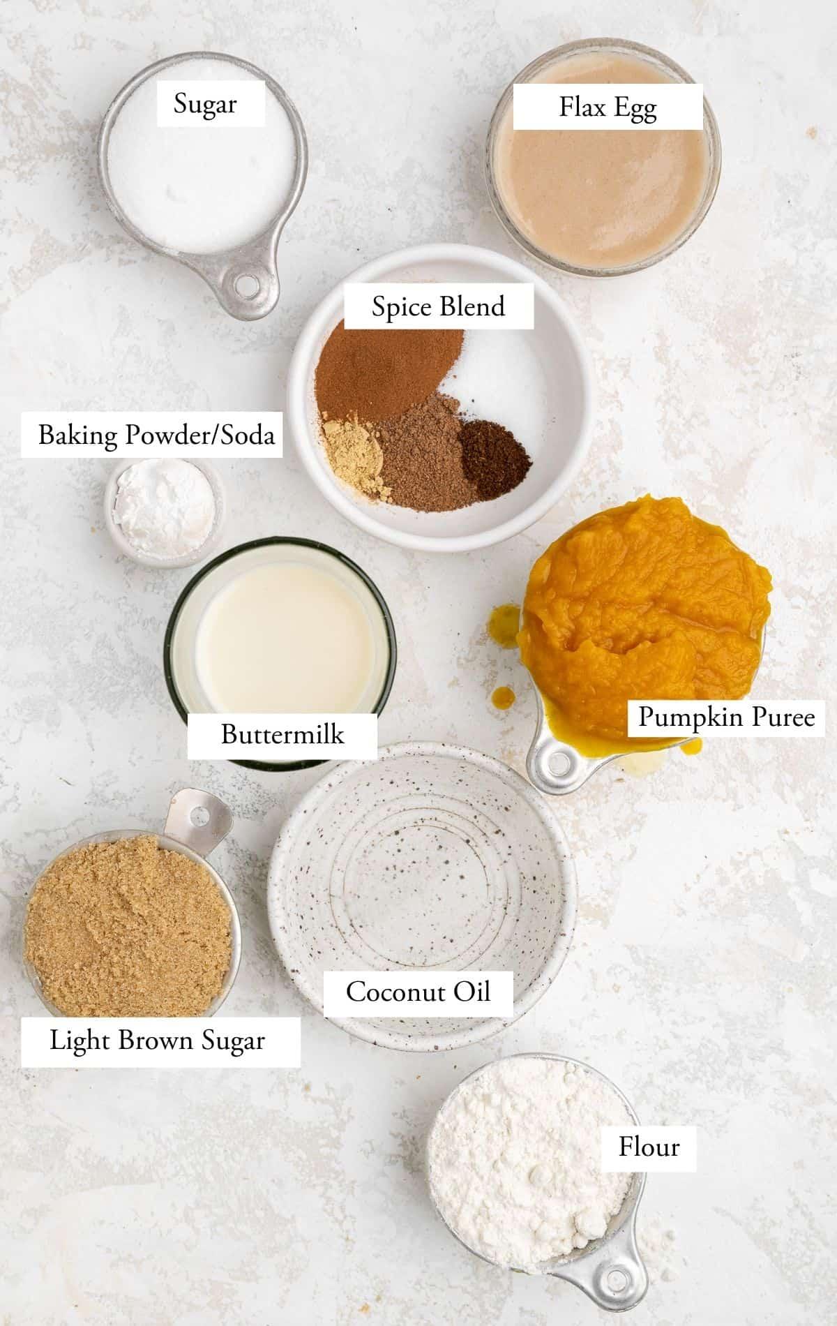 pumpkin coffee cake ingredients on a table: sugars, pumpkin puree, coconut oil, flour, baking powder, baking soda, buttermilk, flax eggs, spice blend.