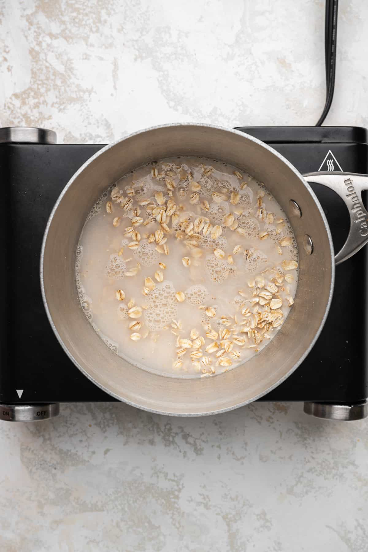 old fashioned oats, non-dairy milk, water, and salt in a stainless steel pot.