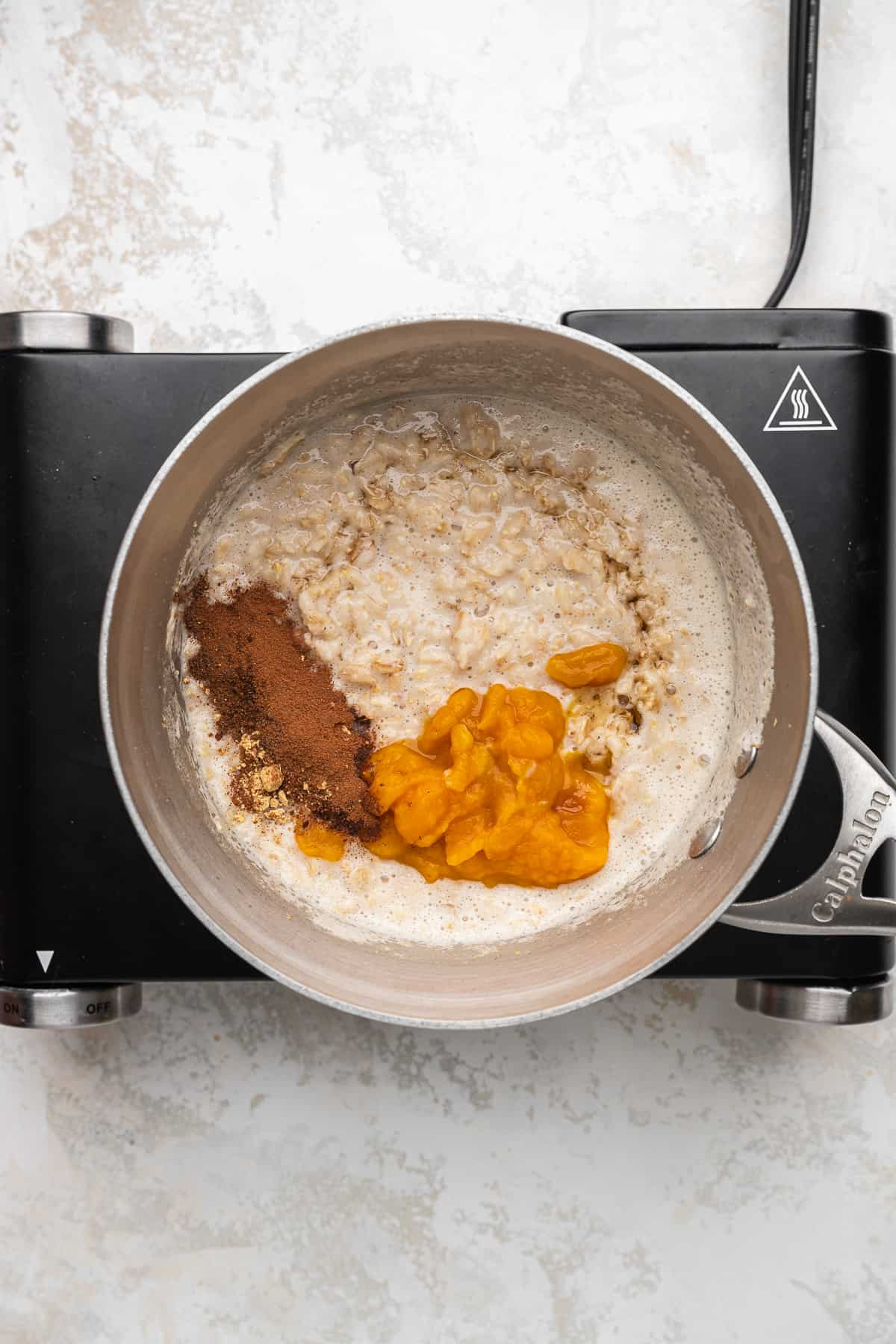 oatmeal with pumpkin puree, maple syrup, and spices cooking in a stainless steel pot.