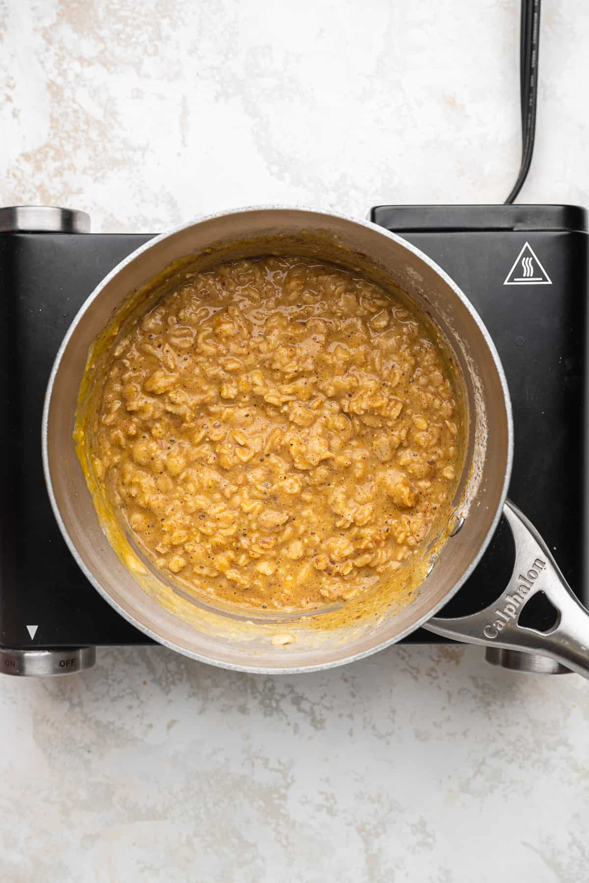 cooked vegan pumpkin oatmeal in a stainless steel pot.