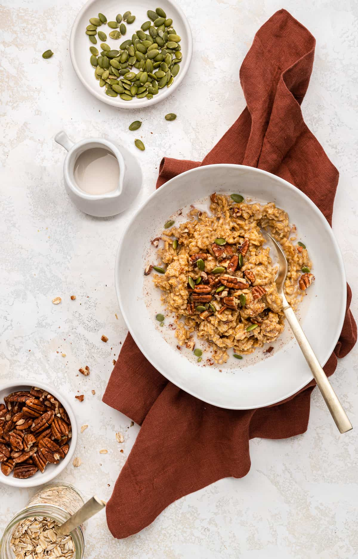 pumpkin spice oatmeal topped with pumpkin seeds, pecans, and maple syrup.