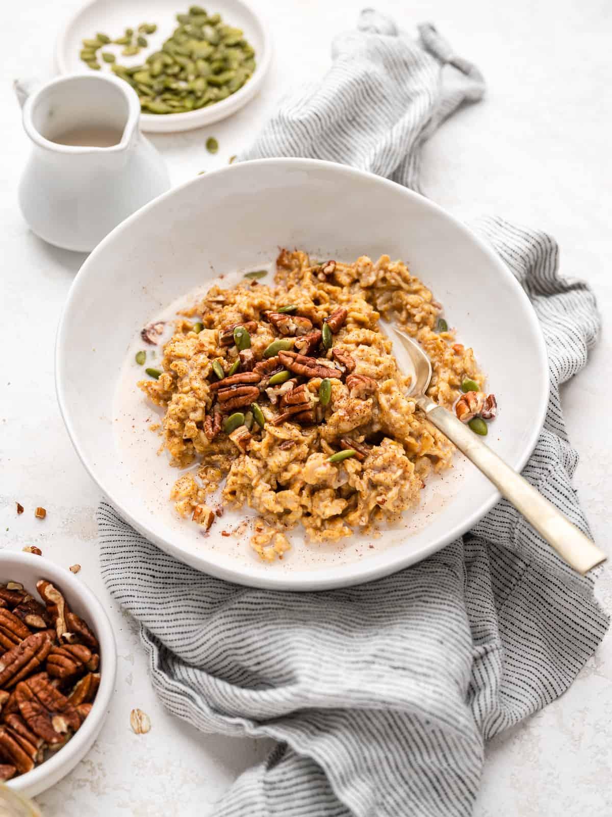 vegan pumpkin oatmeal in a bowl topped with heavy cream, pumpkin seeds, pecans, cinnamon.