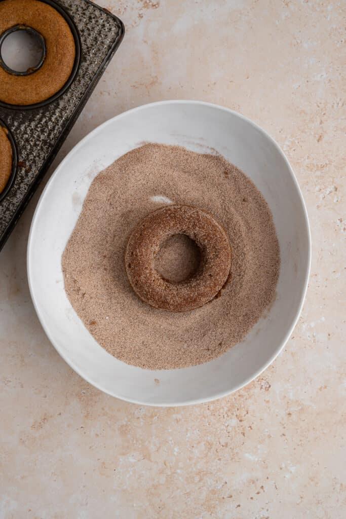 baked donut being dipped in cinnamon sugar.