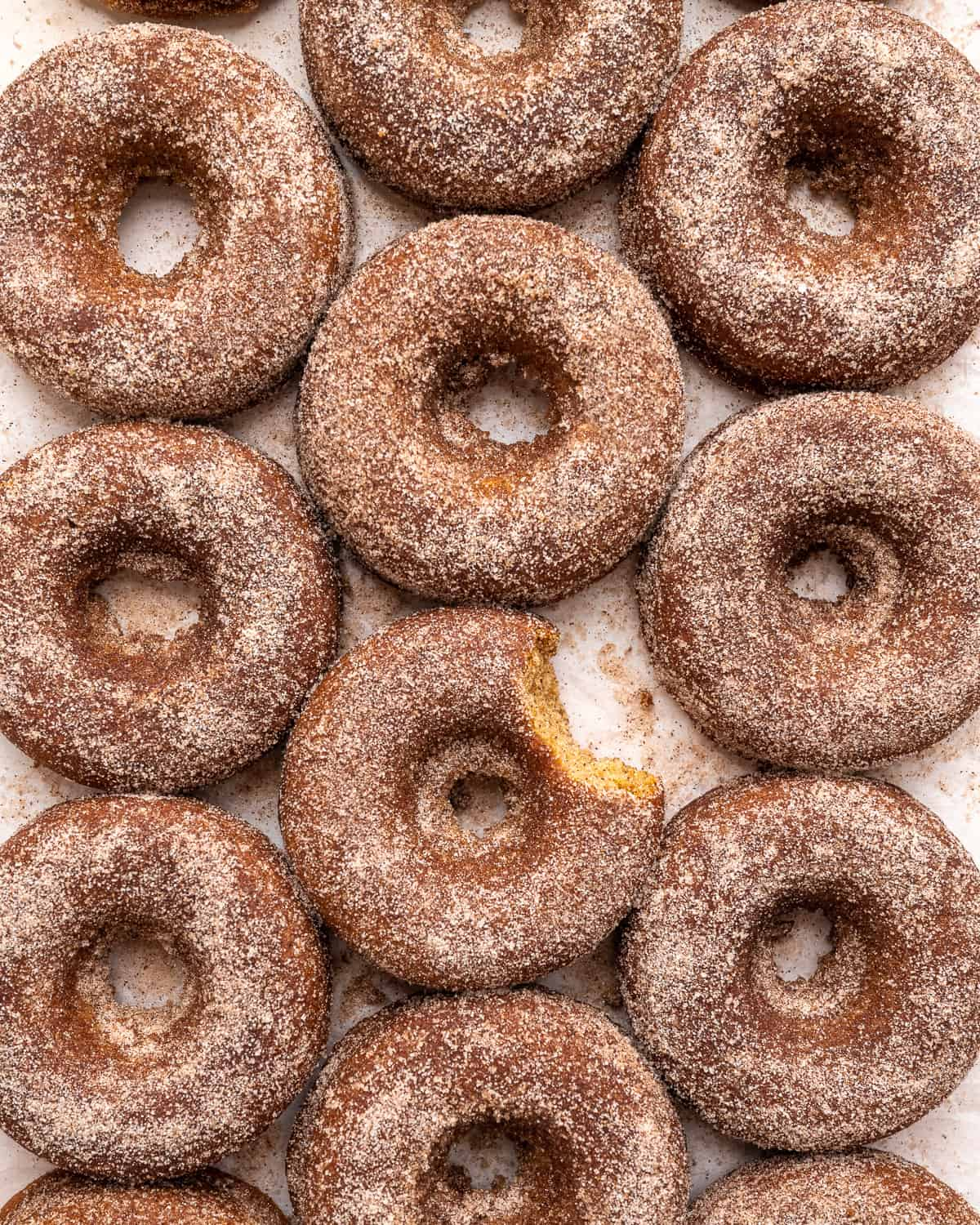 apple cider donuts lined up next to each other on parchment paper.