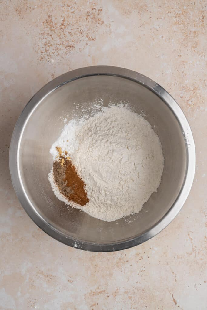dry ingredients for vegan apple cider donuts in a bowl: flour, baking powder, baking soda, spices.
