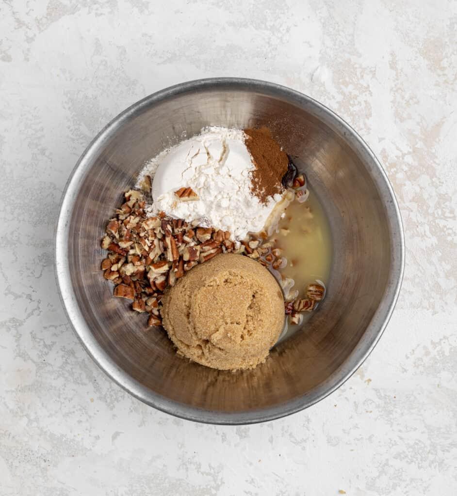 streusel ingredients in a bowl: brown sugar, melted butter, pecans, flour, pumpkin spice.